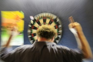 Man with middle finger looking at dartboard