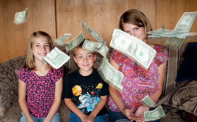 Money falling around three teens, sitting and smiling