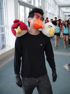Man with plastic beak and two angry birds on his shoulders