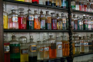 Shelves of old style pharmacy, with coloured bottles