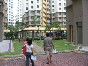Family walking around HDB flats, looking lost and carrying papers