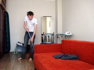 Man mopping the floor of a messy house