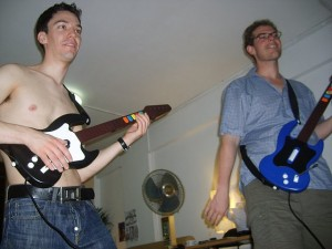Exapts playing guitar hero in a flat