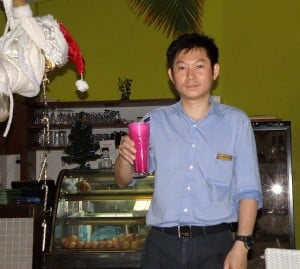 Guy with drink, next to santa claus hat
