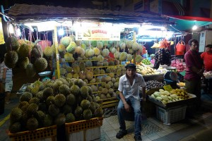Man sitting in front of durian stall