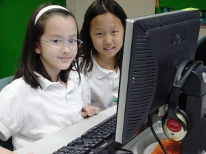 Two young girls using the computer