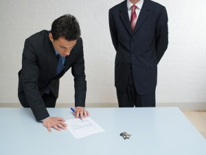 Man signing contract with keys on table