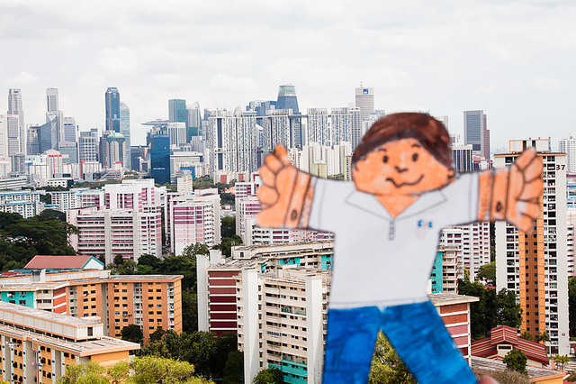 Paper doll in front of city scene, with arms outstretched