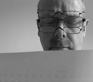 Man with multiple glasses, looking at spreadsheets