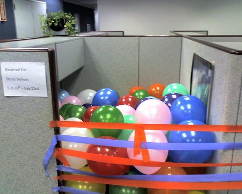 Office cubicle filled with balloons