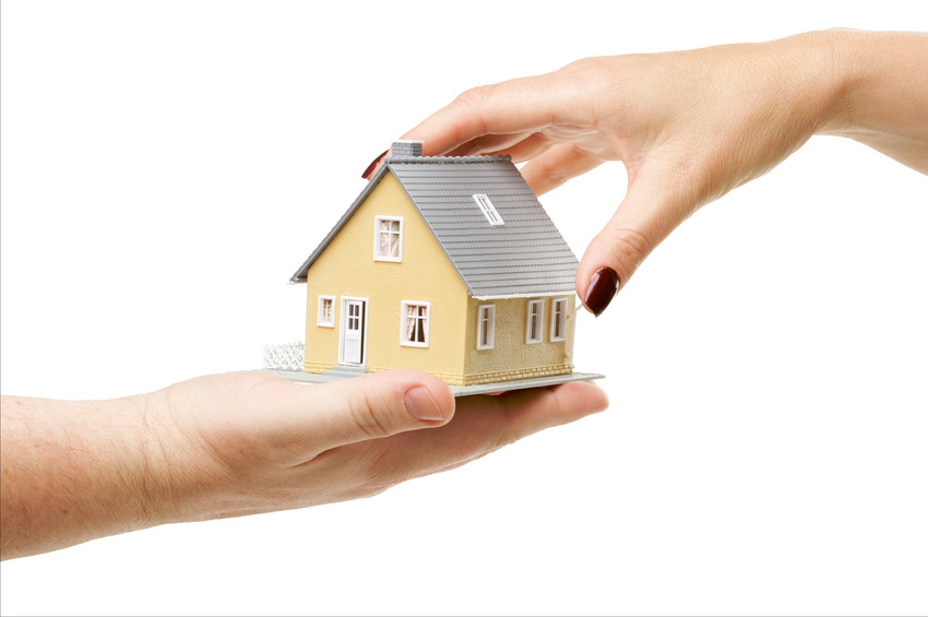 Female hand reaching for a house isolated on a white background.