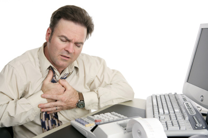 A middle aged man having chest pains or indigestion at work.